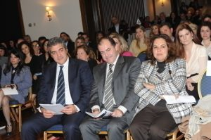 A view of the audience, and in the front row appearing on a l to r basis:: Kostis Moussouroulis, Capt. (HCG) Agisilaos Anastasakos, and Lt. Venetia Kallipolitou