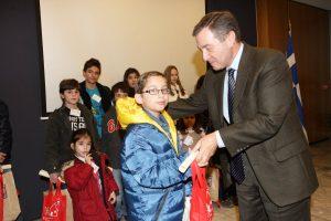 Helmepa Board member Iakovos Perantinos presenting children with their commemorative certificates