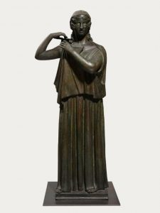 Bronze statue of a woman fastening her dress. From the Villa of the Papyrii, Herculaneum, 1st century BC to 1st century AD. Copyright Soprintendenza Speciale per i Beni Archeologici di Napoli e Pompei/Trustees of the British Museum