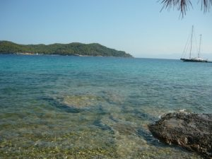 """The """"Kouzounos"""" secluded beach with Spetsopoula at the far end and a yacht at its private pier..."""
