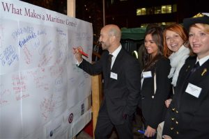 """Phil Parry signs the board of """"What Makes a Maritime centre?"""" in the presence of many female members and guests..."""