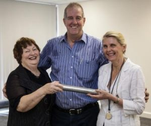 Marilyn Ward and Cathy Pickworth, of the Papua New Guinea Heart Foundation,  holding the baton with Bob Bennett, General Manager, ISS Port Moresby