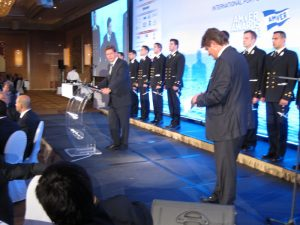 Miltiades Varvitsiotis at the podium with george Xyradakis on his right and officers from the Greek Coast guard on stage