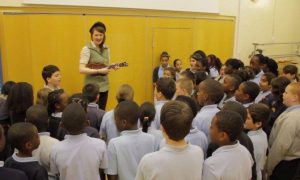 Children aged 10 to 11  at Keys Meadow Primary School, Enfield, learn the chorus of Katy's song Kommander's Car, with Katy on ukulele.