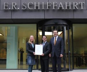 """Kathrin Stürzekarn, Team Leader Maritime Academy Germany at DNV GL, and Christian Heitmann, DNV GL Key Account Manager Business Development Germany, hand over an """"Energy Efficiency on Board"""" e-learning license to Ronald Schnitter, Director Fleet Personnel at E.R. Schiffahrt."""