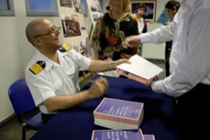 Horacio Vázquez signing copies of his book Women in the Merchant Marine of Argentina