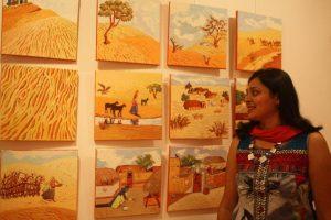 Namita Jain with her panels of village life in Rajasthan.