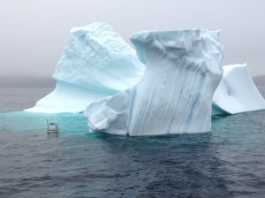 Small experimental unmanned surface craft conducting experiments near an iceberg.