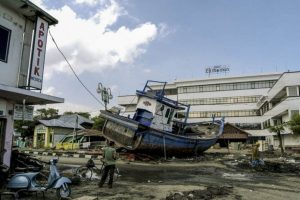 2004: A scene of devastation in front of Hotel Medan in Aceh City centre. The force of the tsunami swept fishing boats like this one hundreds of metres inland, crashing into the city and destroying anything along the way. WFP/Rein Skullerud