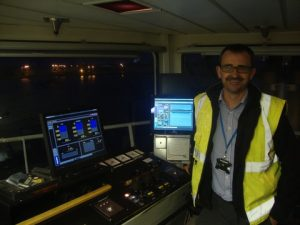 Mr Paul Mitchell at the dredge masters desk showing left the Load and Draught screen and right the Trailing Pipe Monitoring screen LOW RES