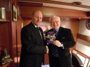 Rodney Croft presents a copy of his book to Havengore owner Chris Ryland in his cabin.