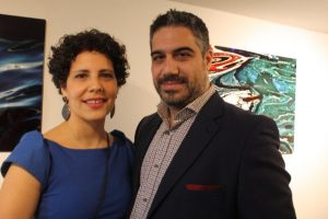 Kitsa Angelakos and husband Anargyros Skinitis with her prints Waves II and Subconscious Series 5 in background.