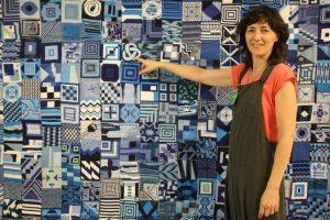 Alejandra Corral (Kuska) with Black Tears Project tapestry.