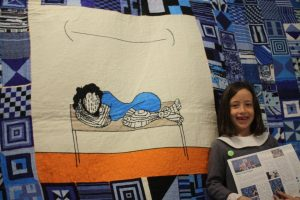 Young supporter Ada admires Black Tears tapestry.