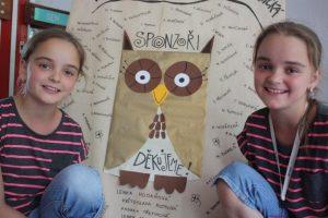 Twins Vendula and Teresa, with school logo.