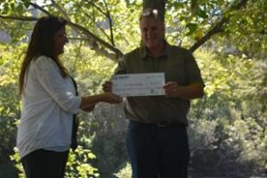 CEO Paul Hill gives the check to Curry County Director of Administration Julie Schmelzer