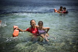 """Volunteers from the Spanish group 'Proem-Aid' teach refugee children from """"PIKPA village"""" how to swim. For many of the youngsters, who endured terrifying sea crossings from Turkey, it is a skill that will change their lives forever. Photo: UNHCR/Gordon Welters"""